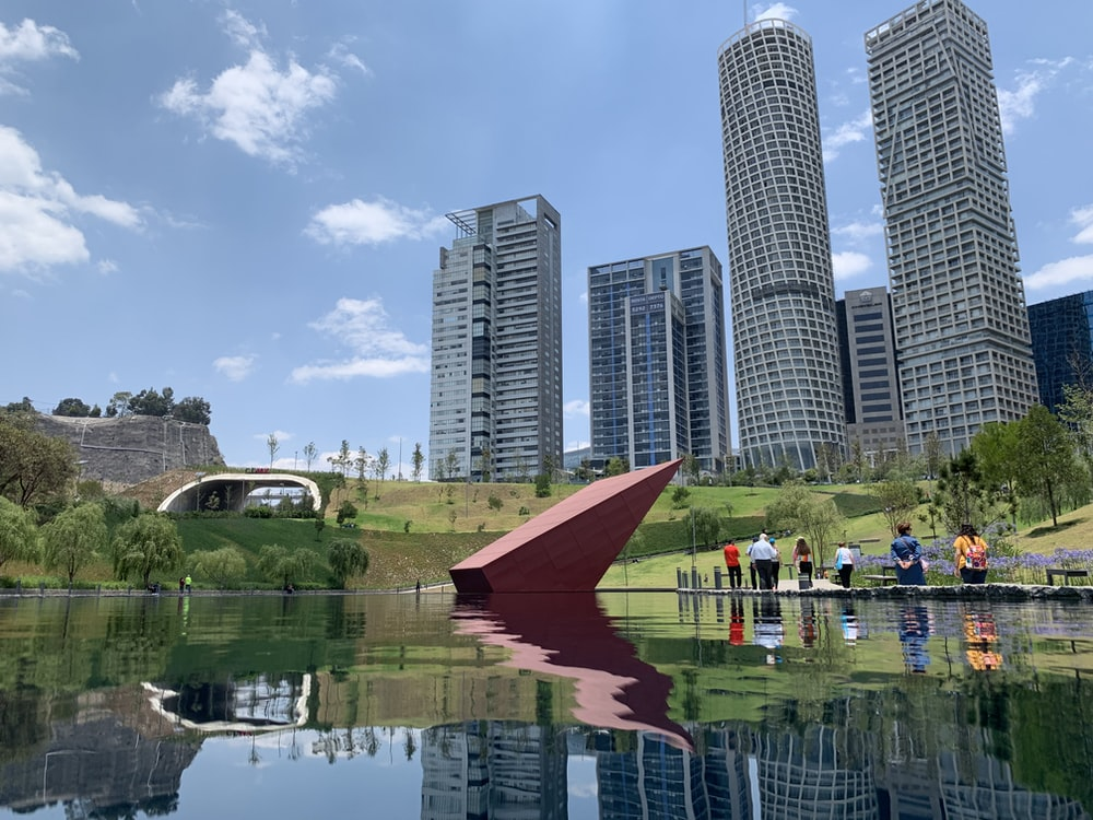 people near green field beside tall and high-rise building under blue and white skies