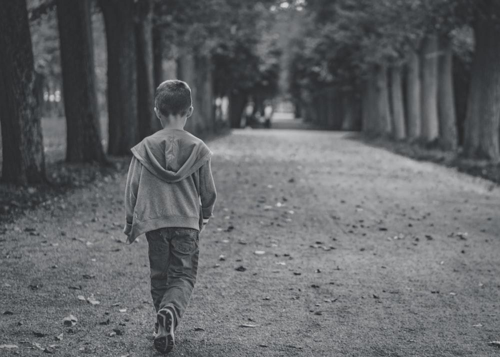 boy walking near trees