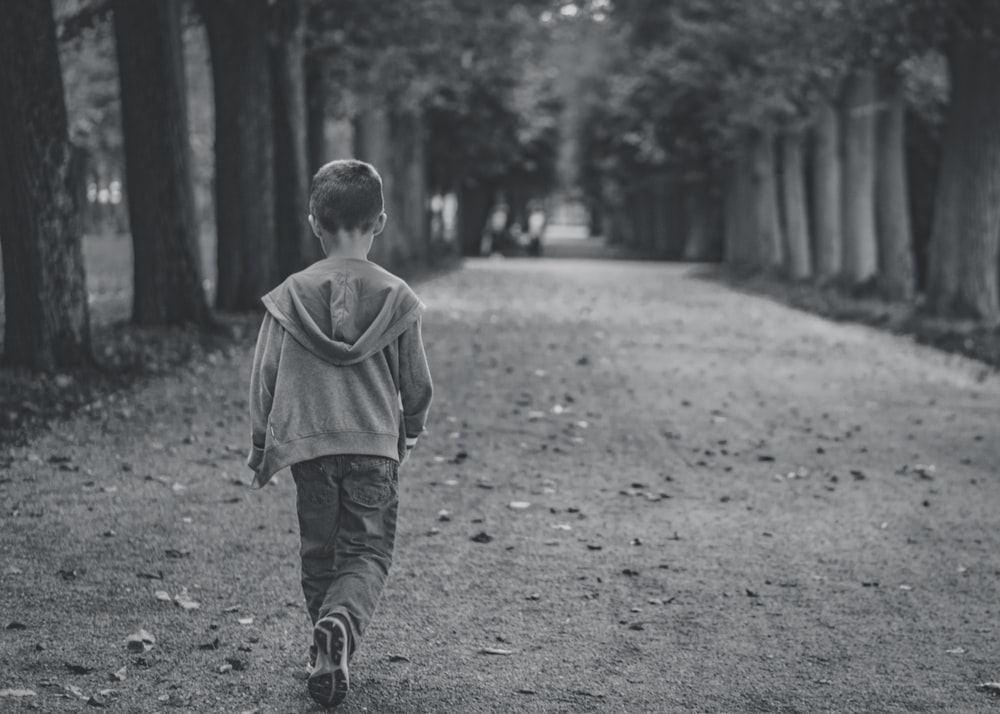 boy walking near trees