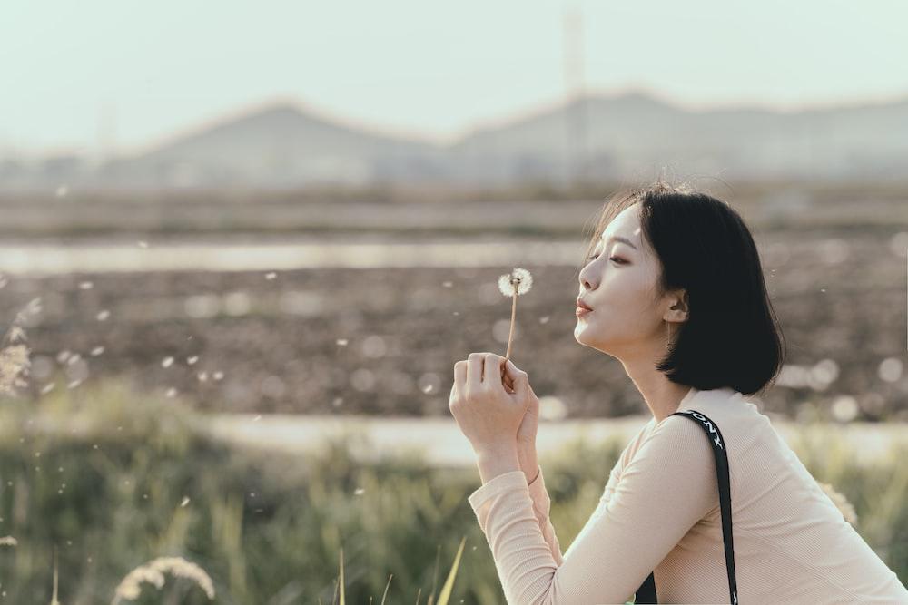 woman holding dandelion