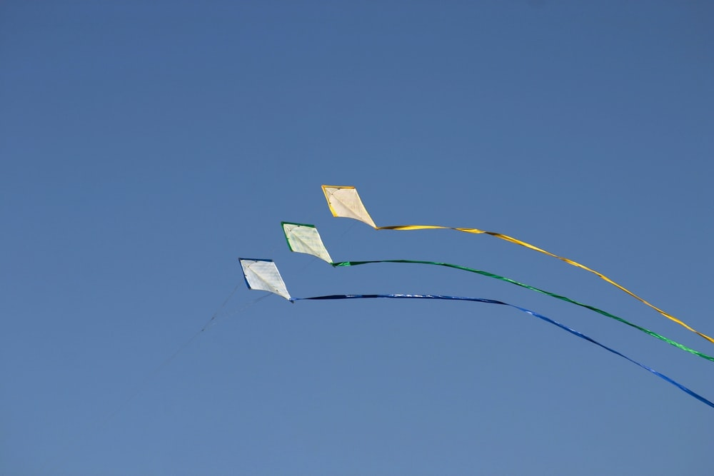 three kites under blue sky during daytime