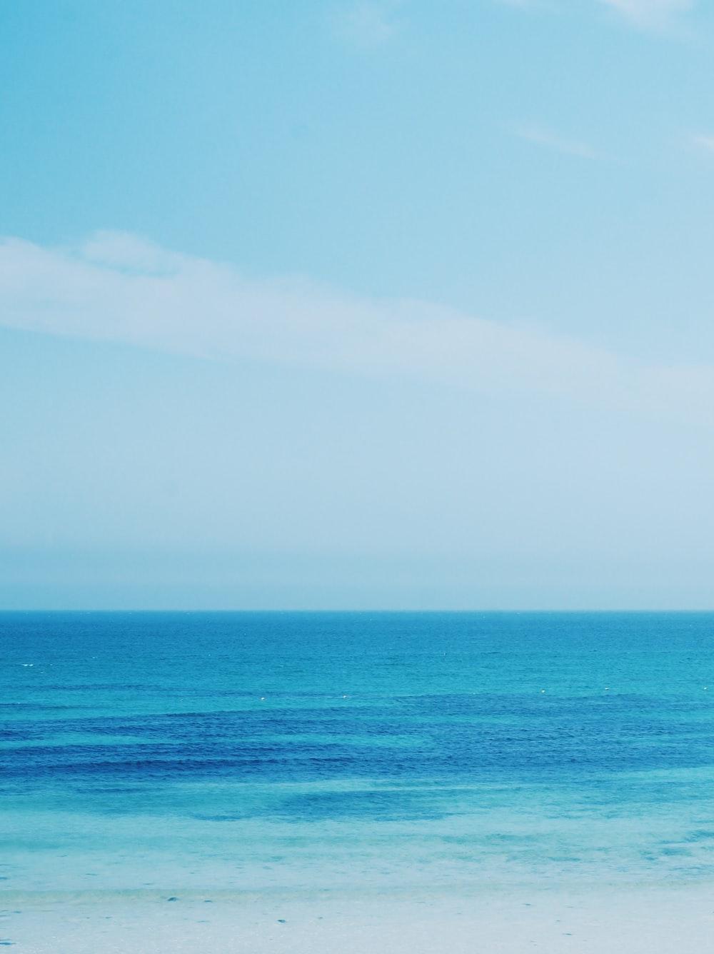 blue beach under clear blue sky
