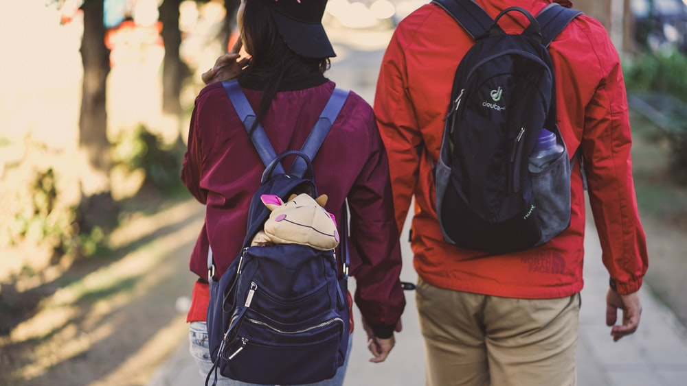 man and woman wearing backpacks