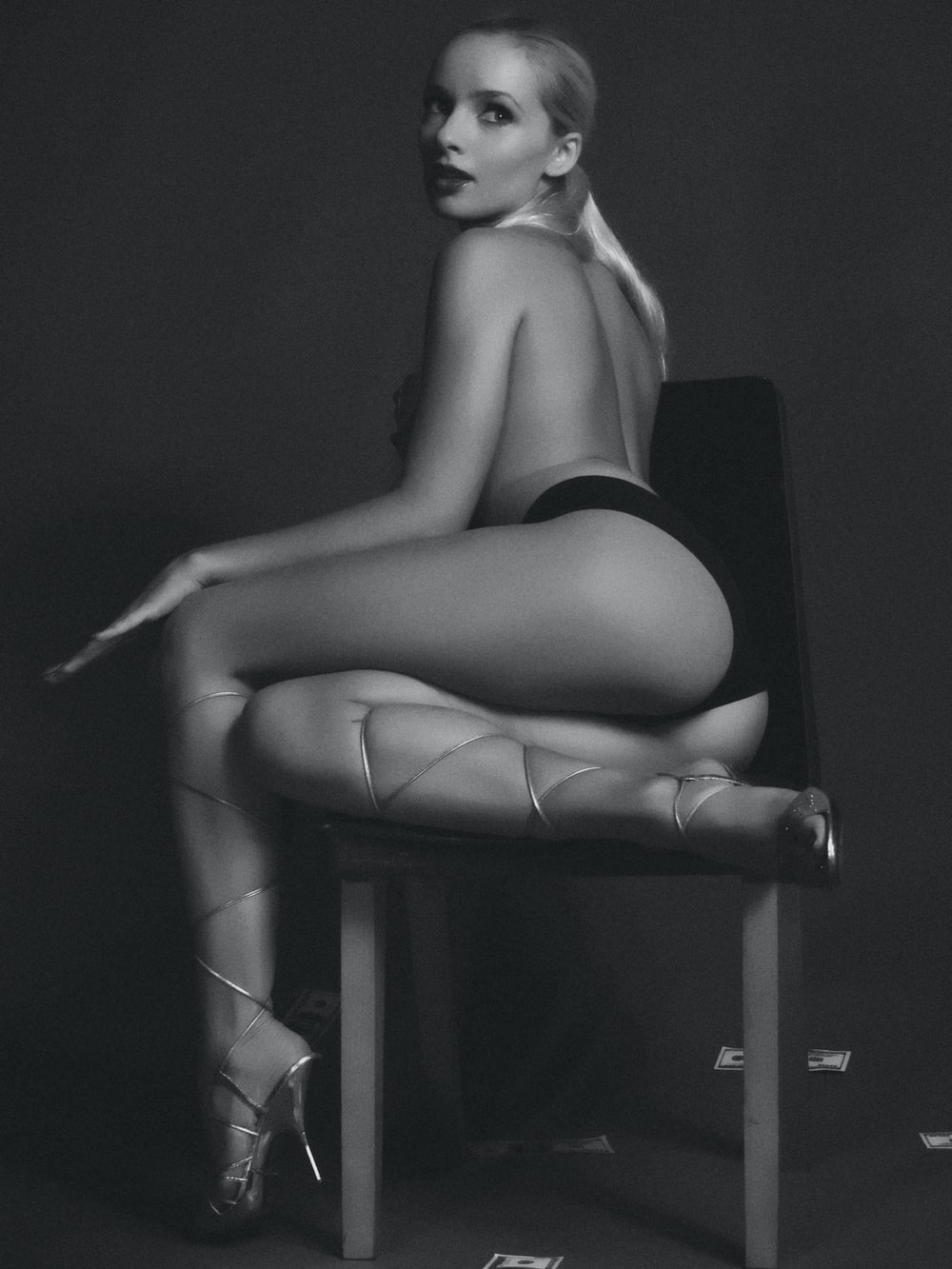 topless woman wearing black panty sitting on chair facing back