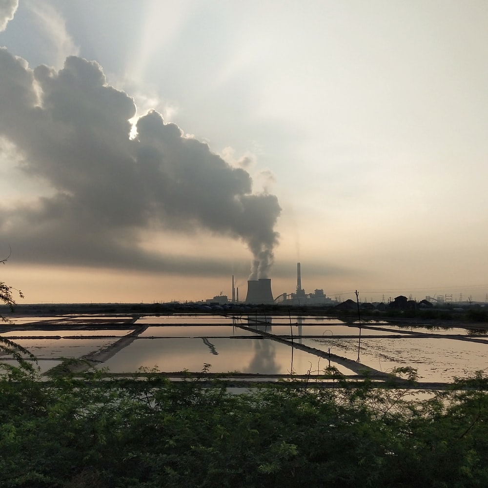 body of water near factory during daytime