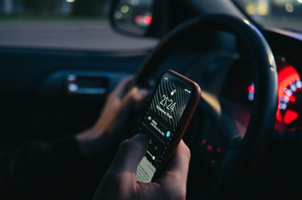 person using iPhone inside vehicle