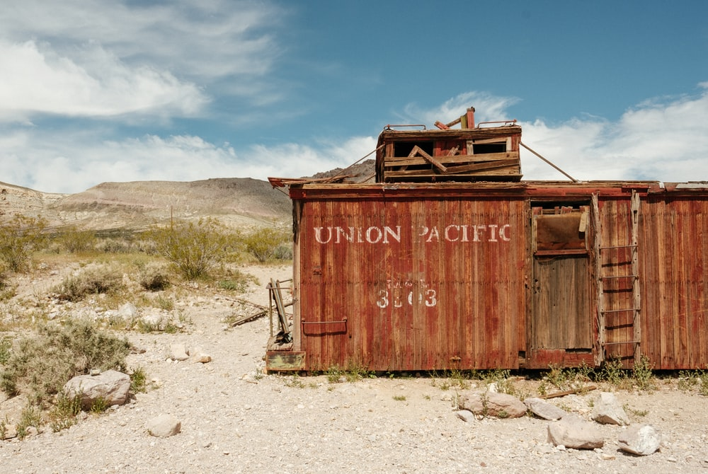 brown dilapidated Union Pacific train car at desert