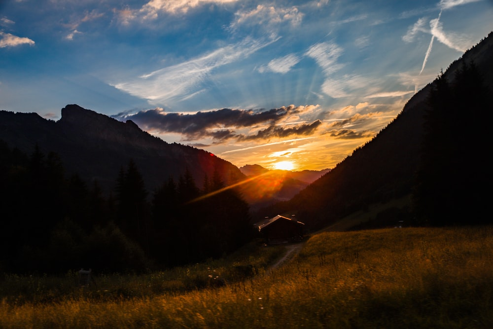 mountain and green field during sunrise