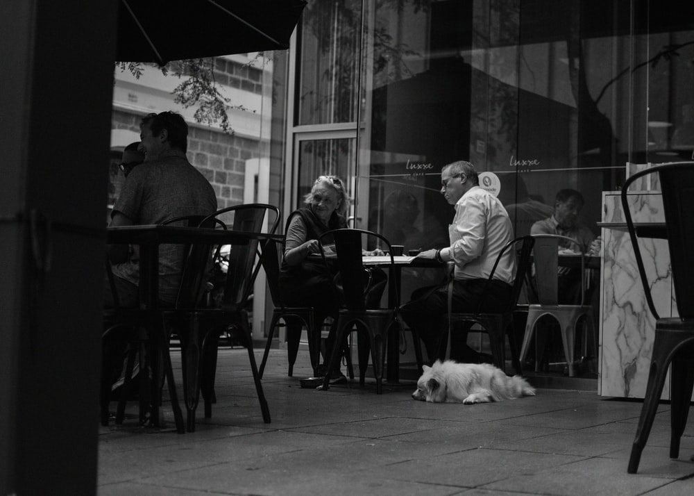 grayscale photo of people in outdoor cafe