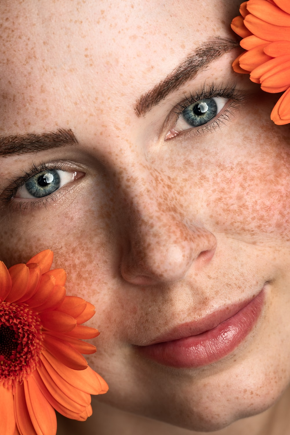 woman with orange petaled flower on the ears
