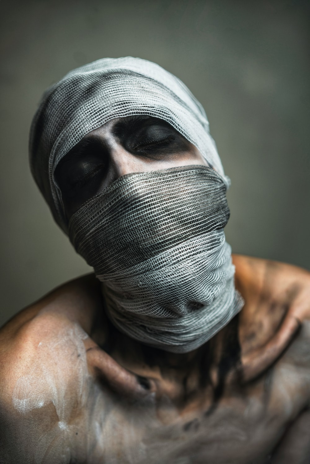 topless person with bandage on face