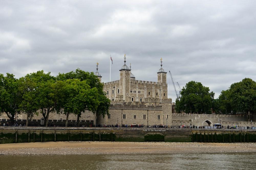people walking near brown concrete castle under white skies