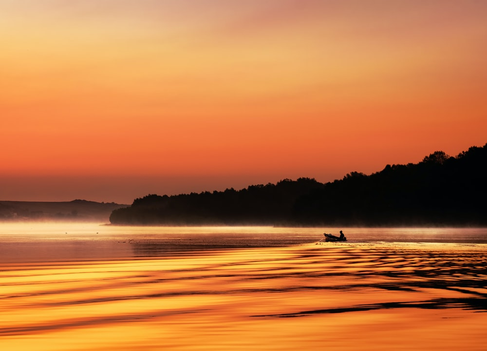 man in boat out at sea during sunset with orange sky