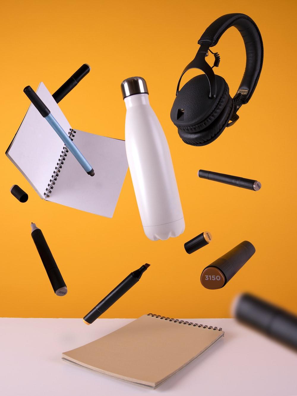 black cordless headphones beside sport bottle and notebook