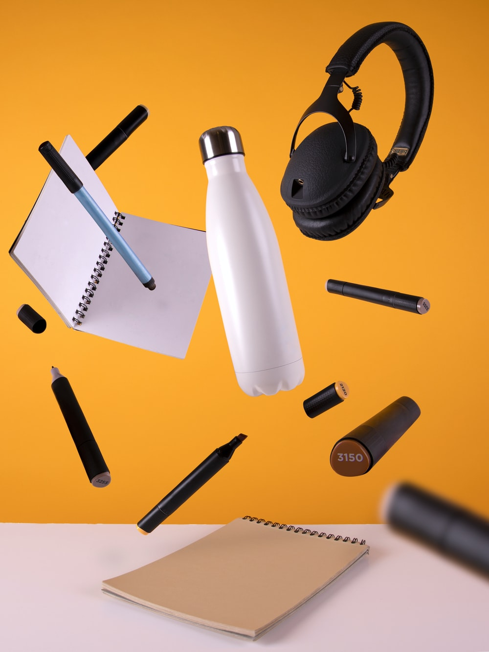 black cordless headphones beside sport bottle and notebook