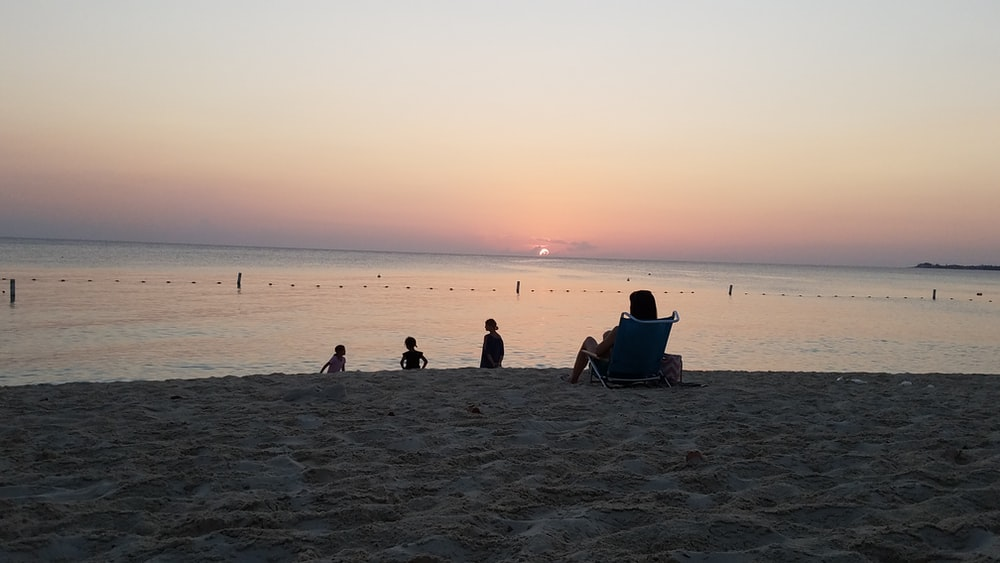 person sitting on lounger facing beach