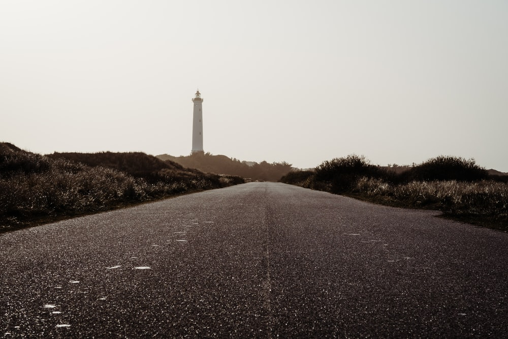 empty road near lighthouse tower