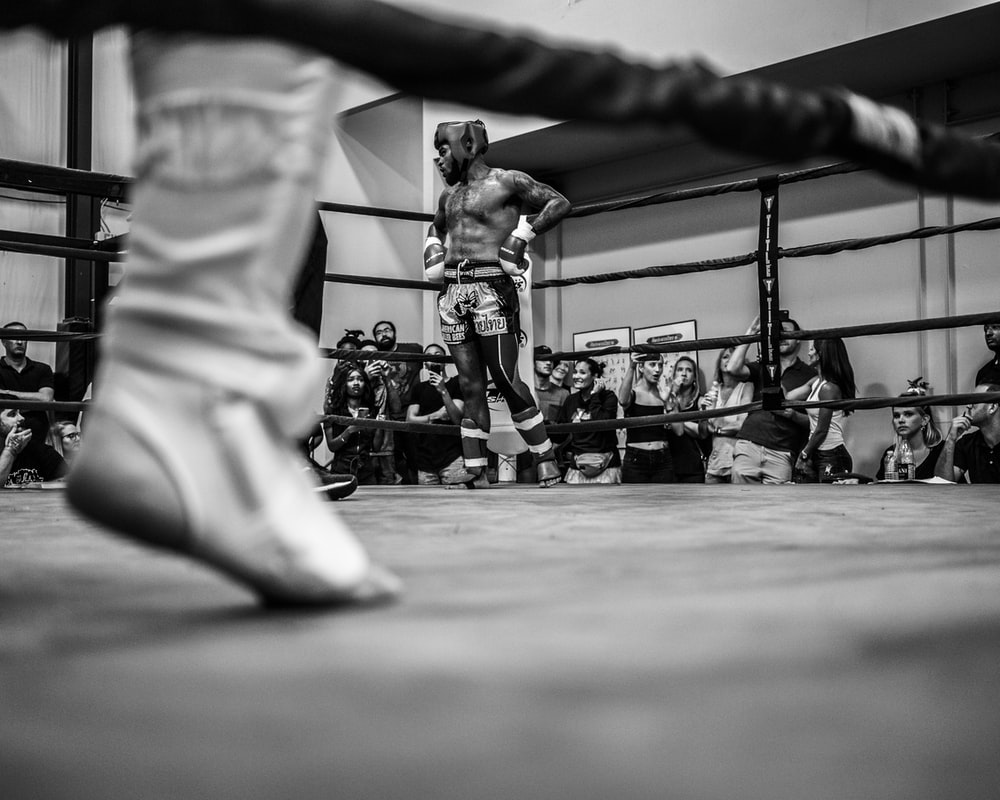 grayscale photo of people watching boxing with man wearing white bottoms inside boxing ring