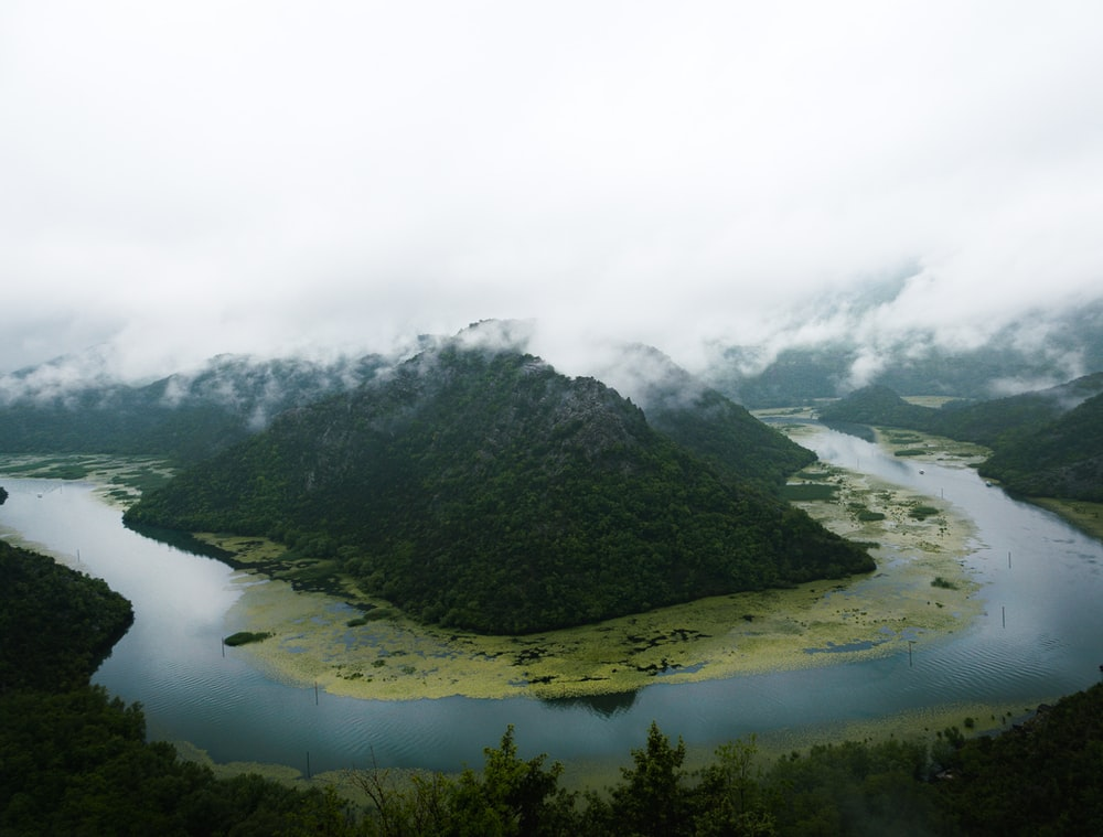 aerial photo of river and mountain during cloudy day