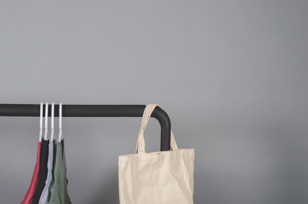 white tote bag hanged on metal rack