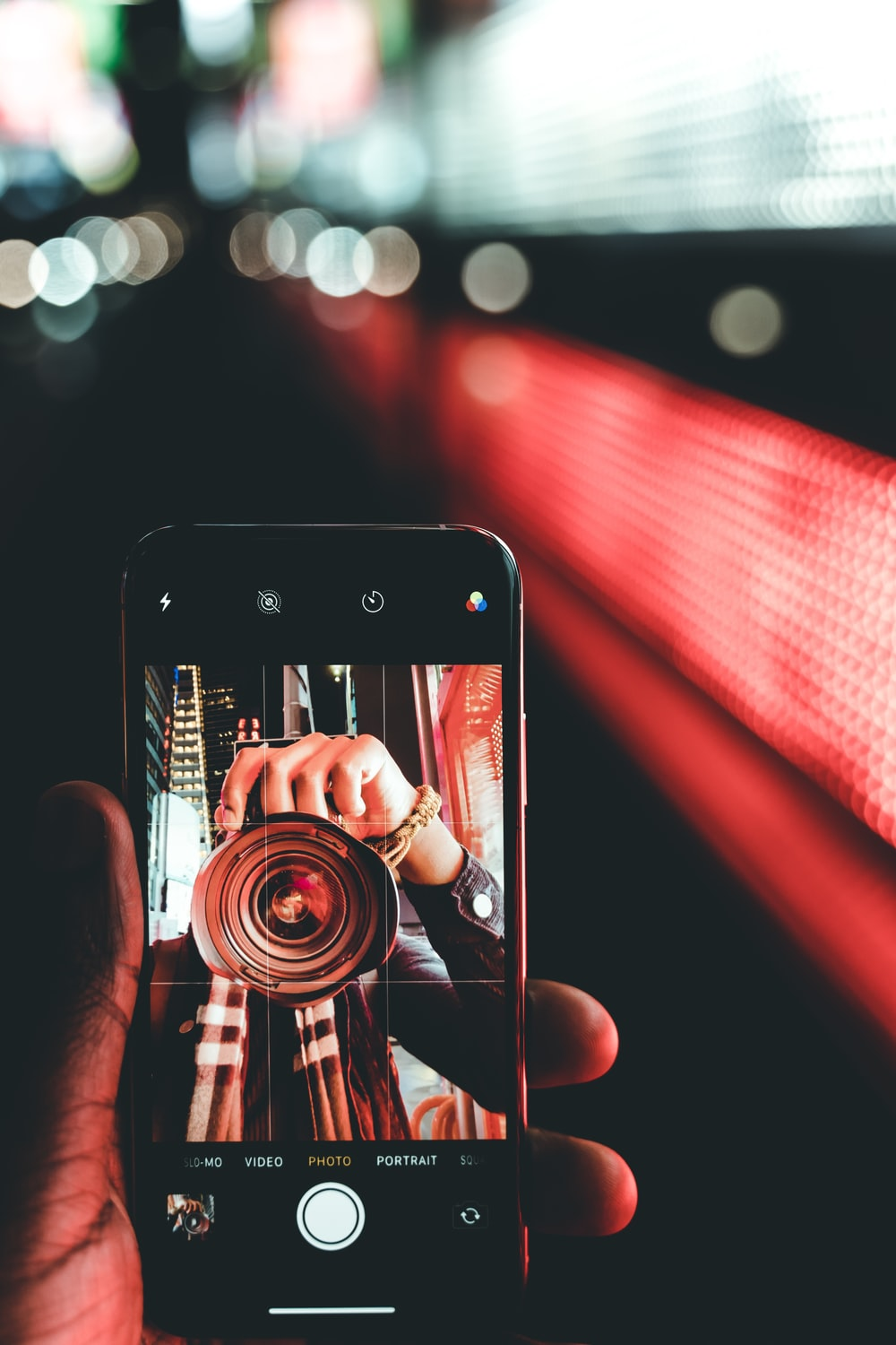 smartphone showing person holding DSLR camera