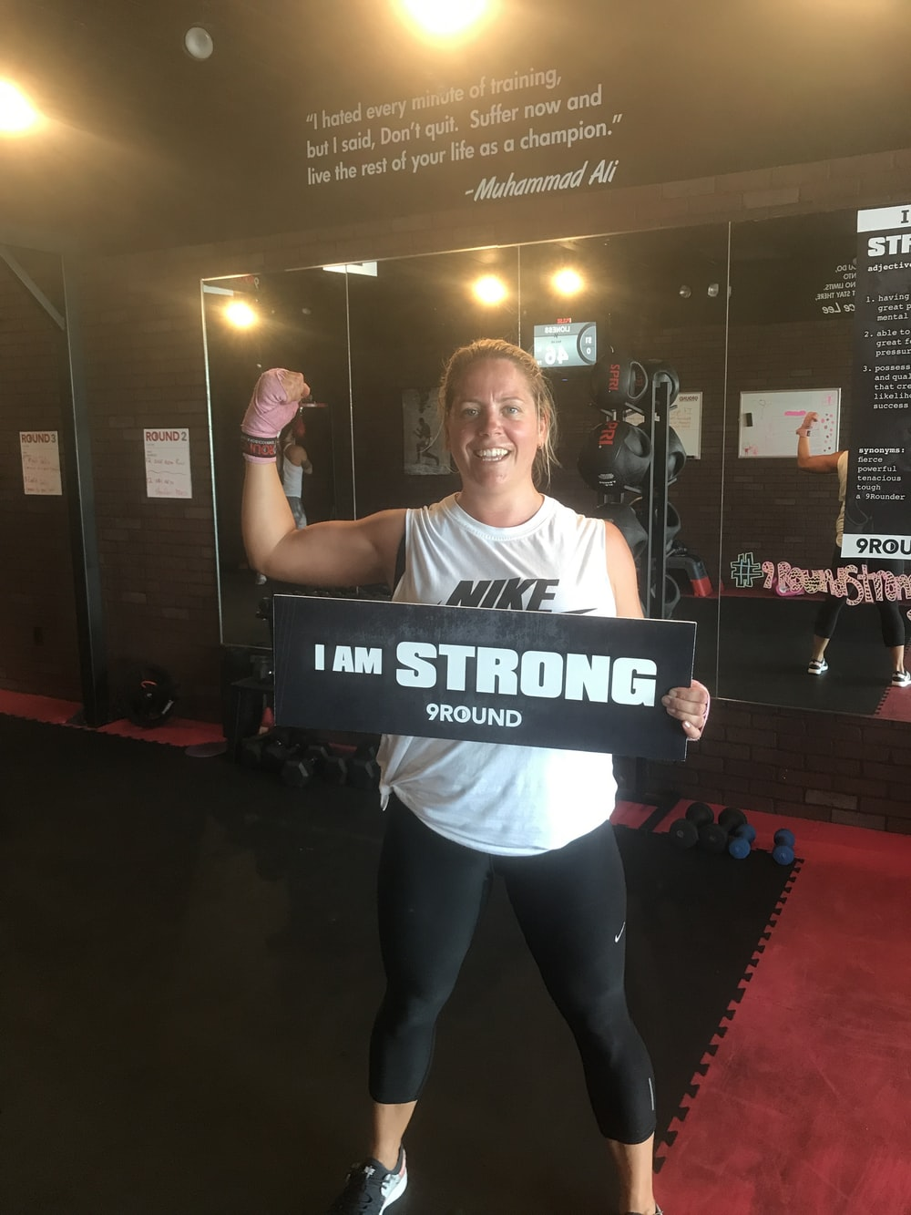 woman standing holding i am strong 9 round signage