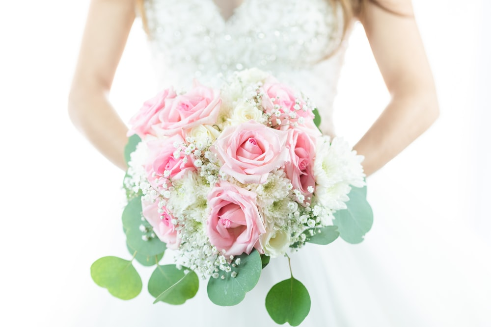 woman holding pink and white rose flower bouquet
