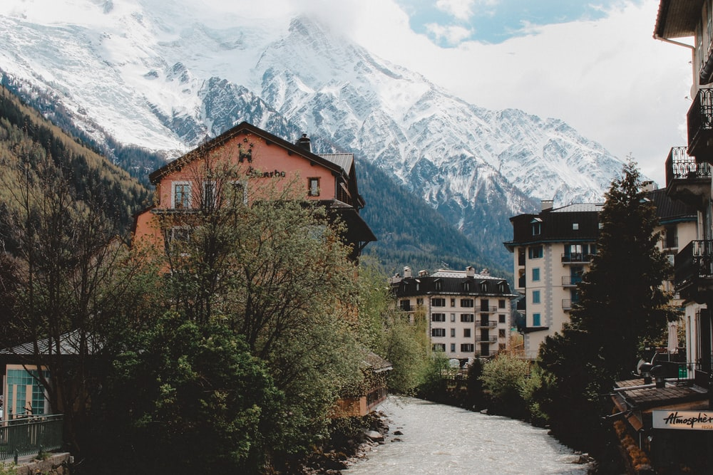 buildings near trees and glacier mountains at the distance during day