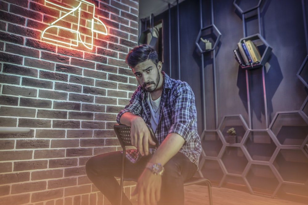 man sitting on chair beside brick wall