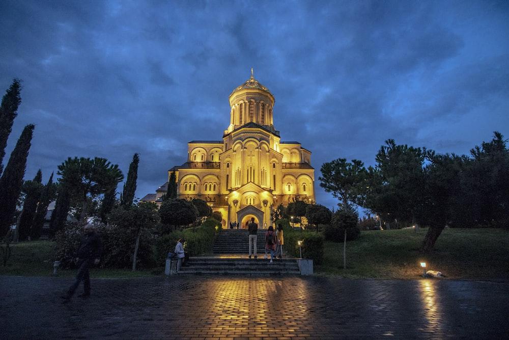 people walking near concrete church during night time