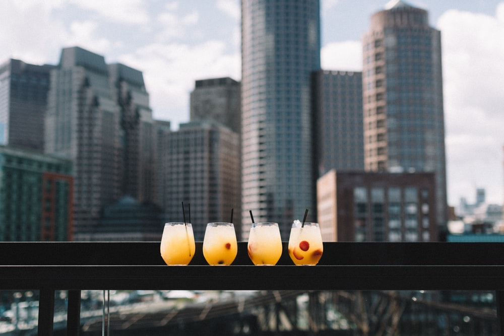 four drinking glass on black surface during daytime