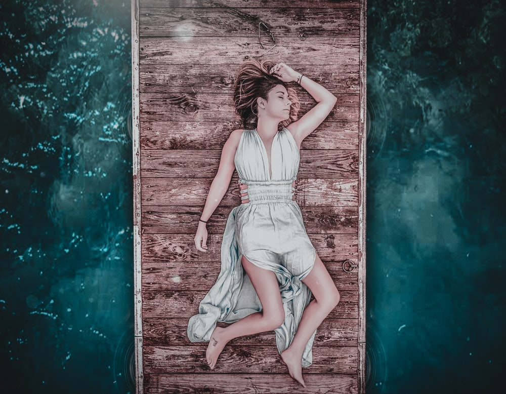 woman lying on brown wooden dock