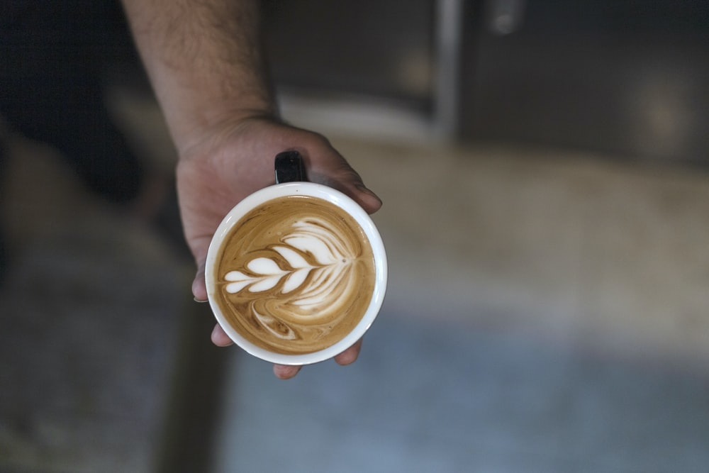 person holding leaf latte