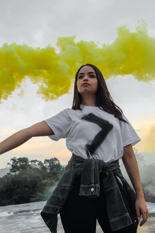 woman holding yellow smoke bomb