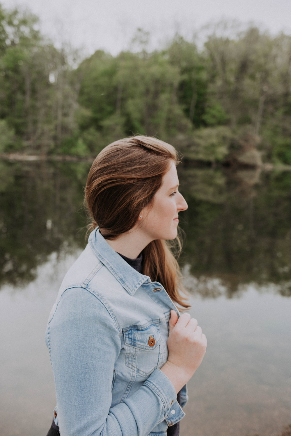 woman in faded blue denim jacket standing in bank of lake