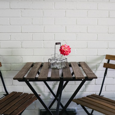 brown folding table and chairs by the white wall