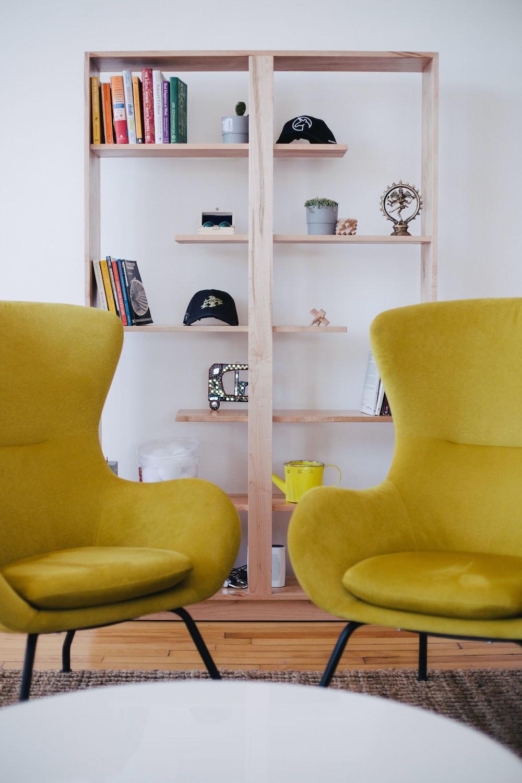 two yellow chairs near brown shelf