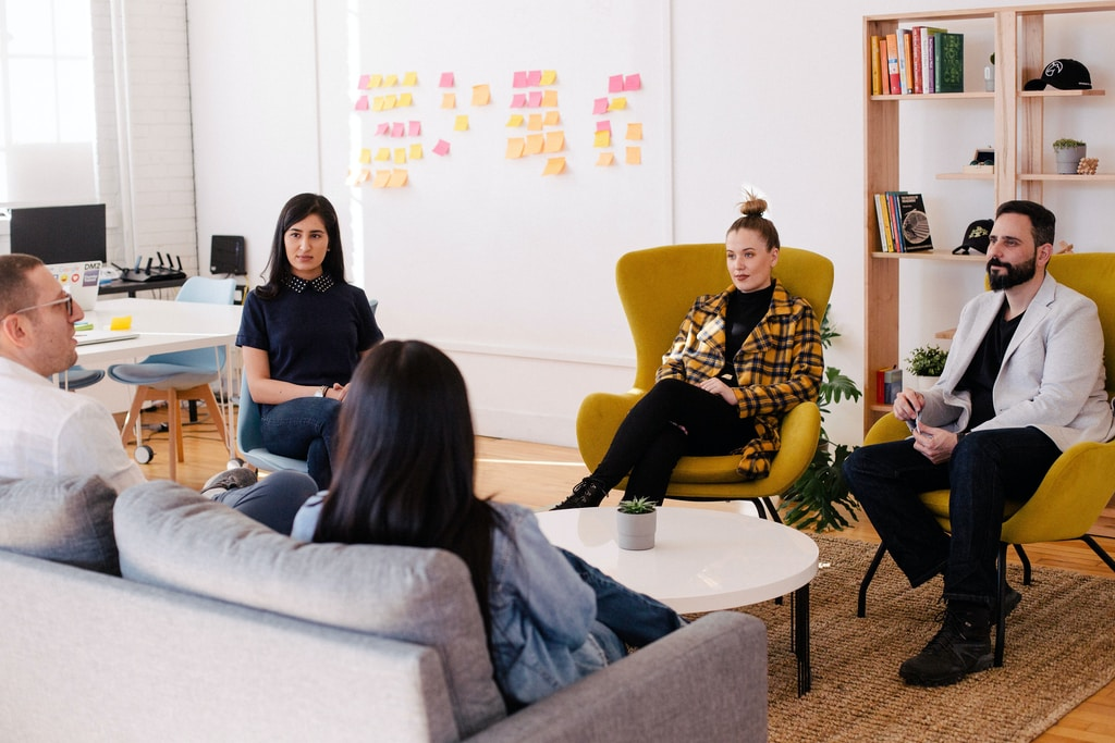 Agile working people seated on table in room