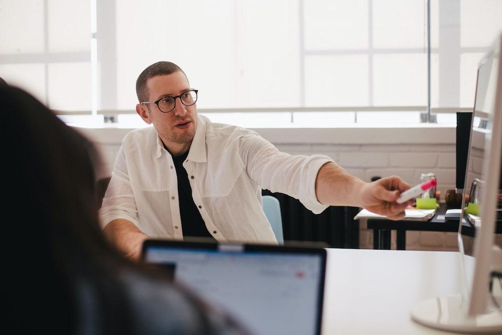 man wearing white dress shirt pointing on monitor