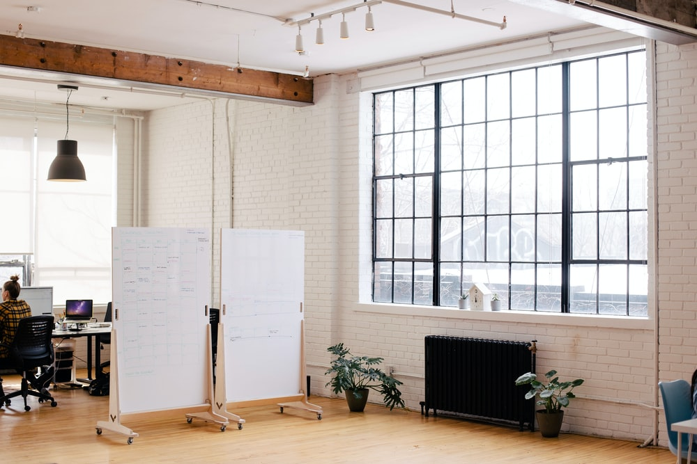 two white projector screens across room