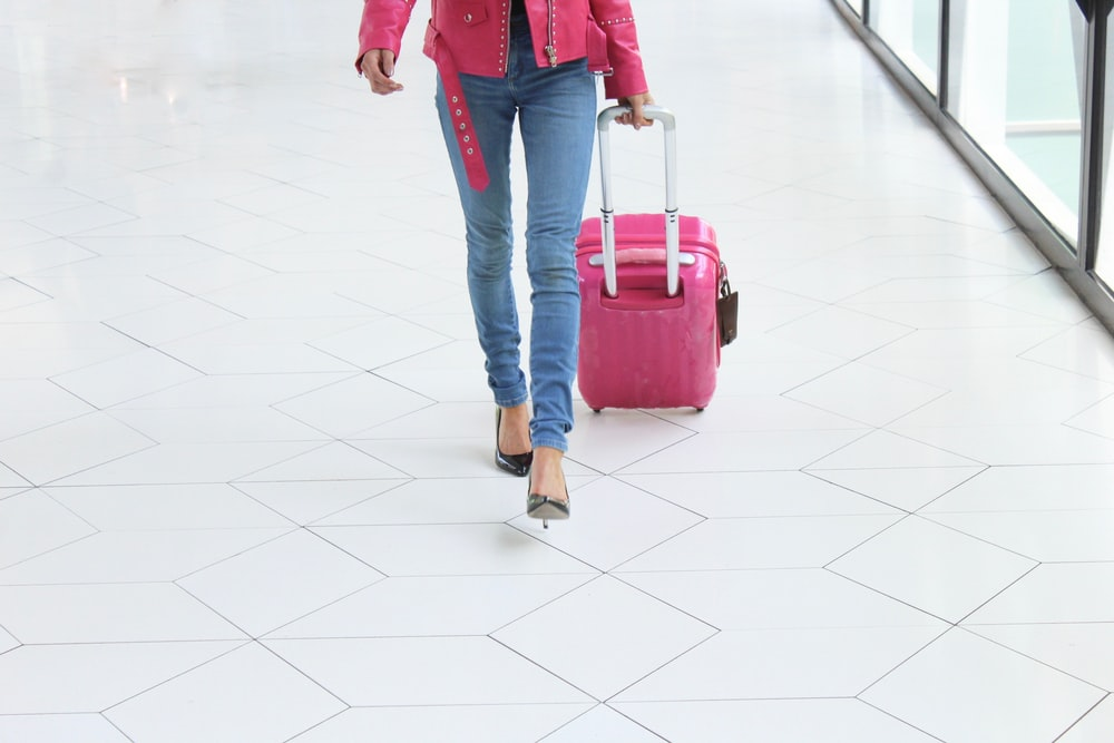 person wearing red jacket and blue denim jeans pulling luggage bag while walking on pathway