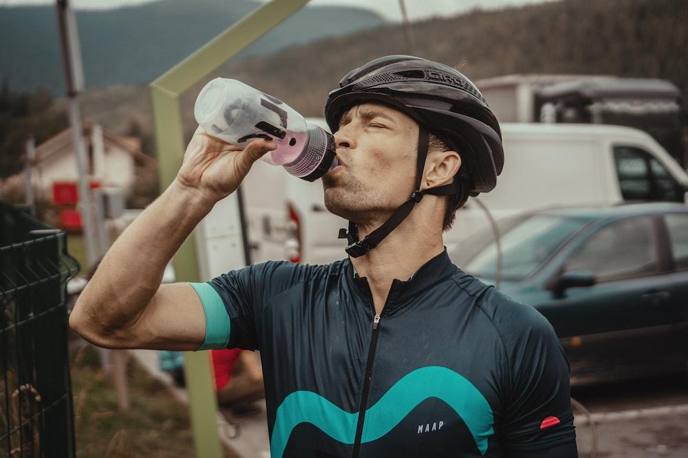 man drinking from a sports bottle wearing biking gear in front of parked cars