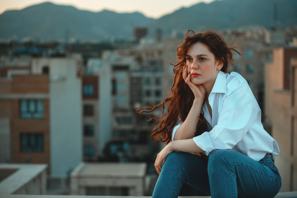 woman in white dress shirt and blue denim jeans sitting at rooftop
