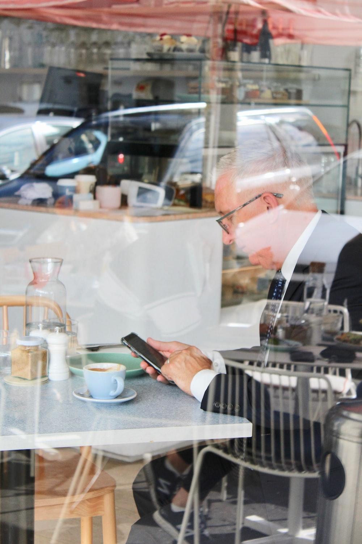 man in black blazer using smartphone in cafe
