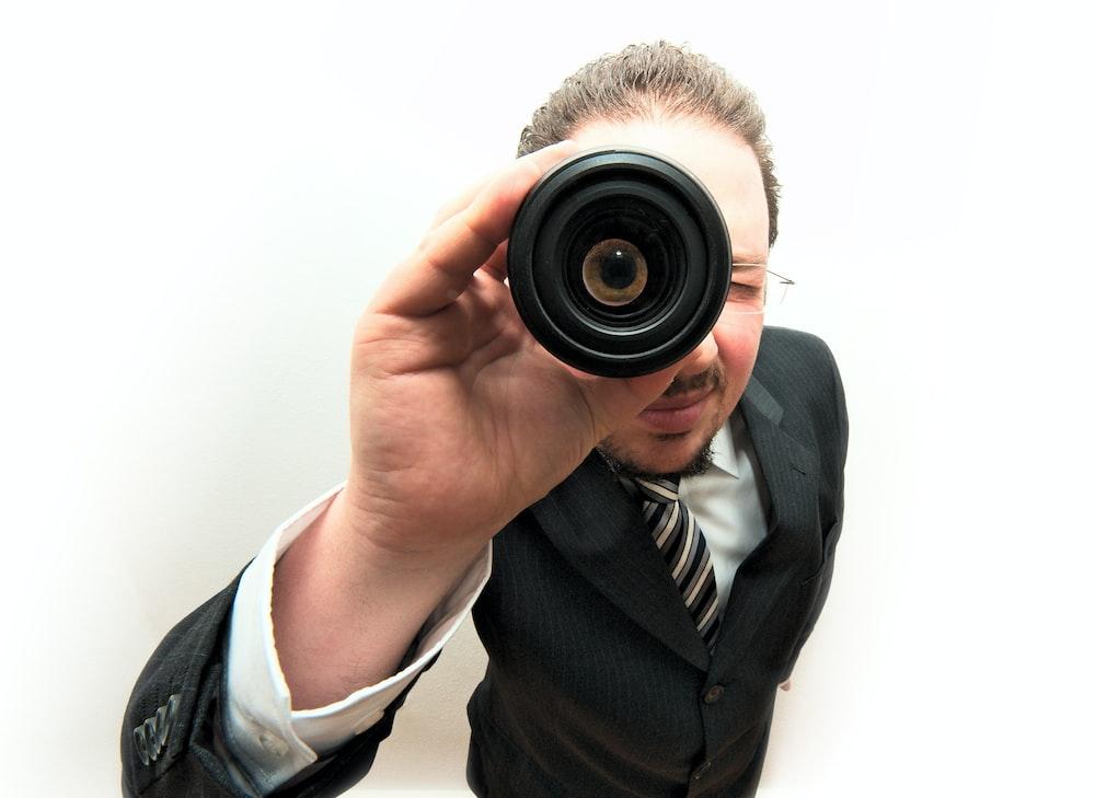 man carefully looking through monocular