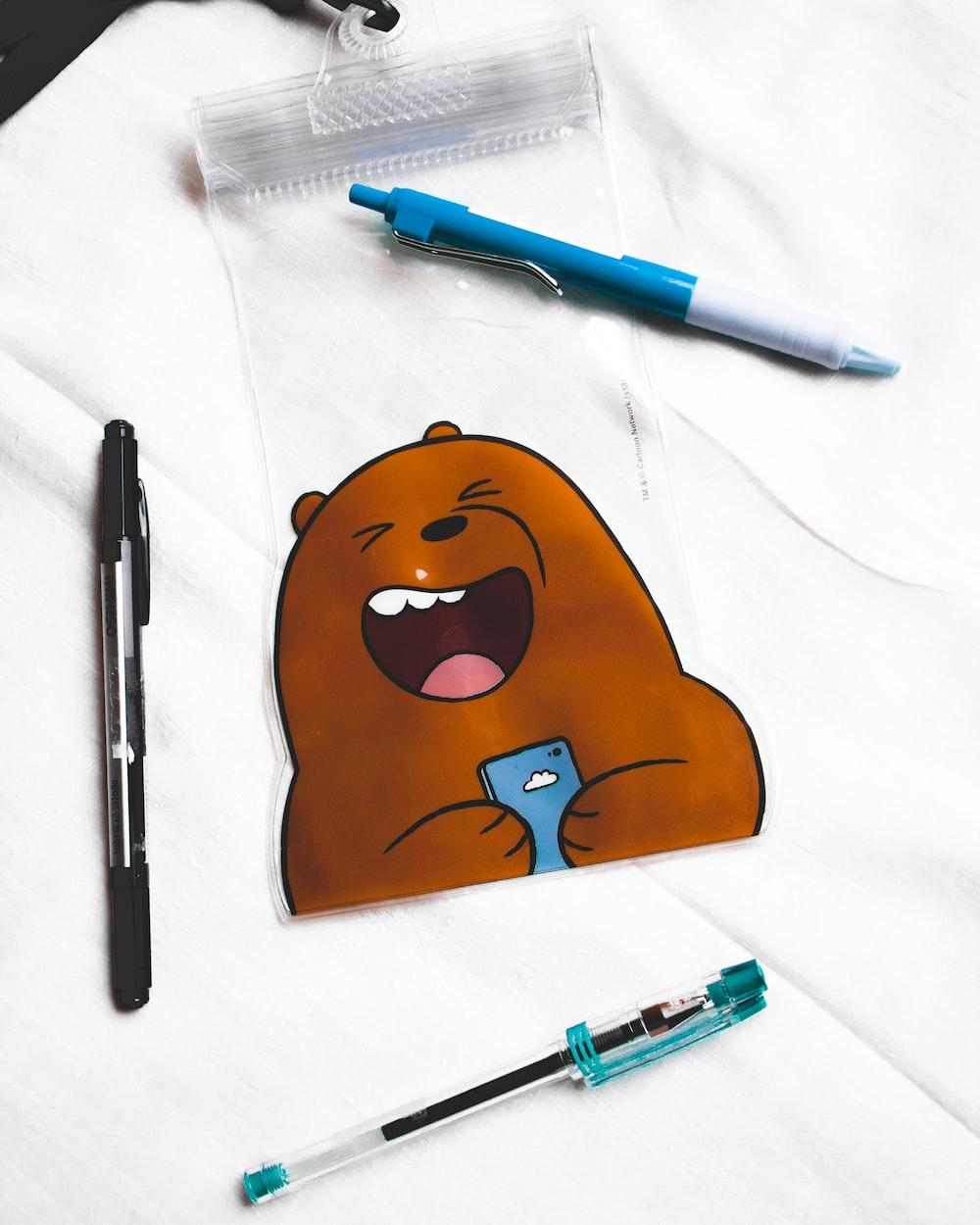 three assorted-color click pens near We Were Bare Grizz mini pouch