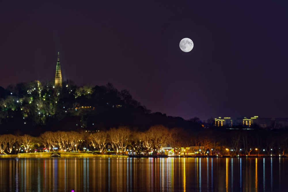 white round moon in dark night sky over lighted city skyline by the bay