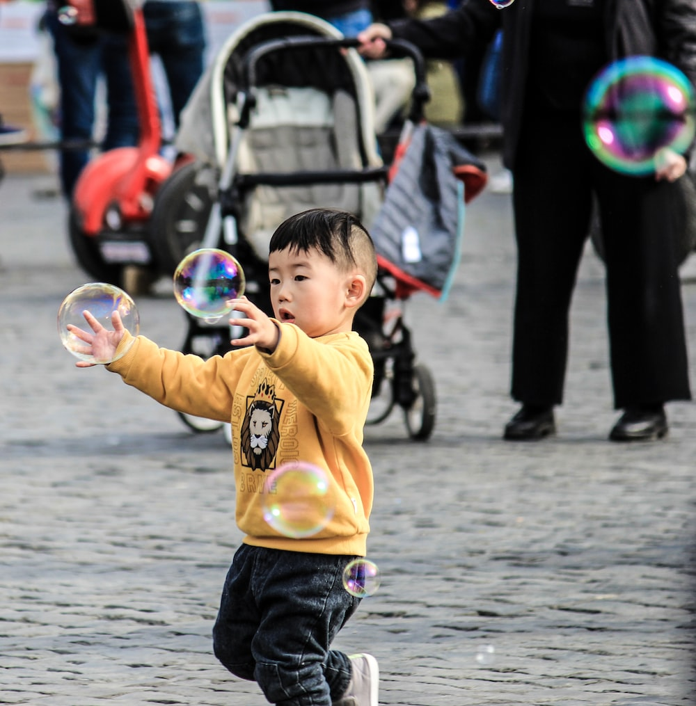 boy in yellow sweater playing with bubbles