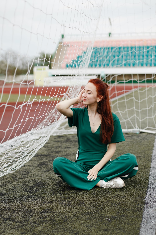 woman sitting in green overalls beside net