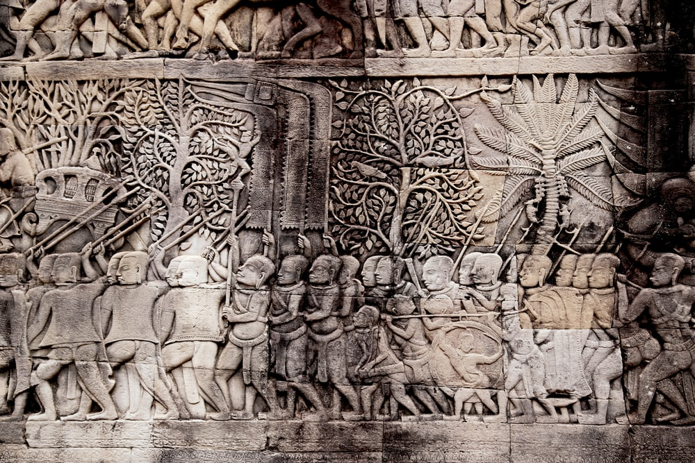people holding spear embossed wall